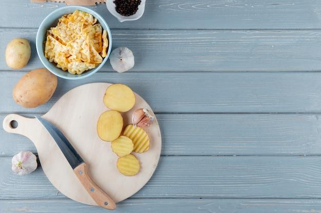 Vista cercana de rodajas de patata y ajo con cuchillo en la tabla de cortar y patatas fritas sobre fondo de madera con espacio de copia