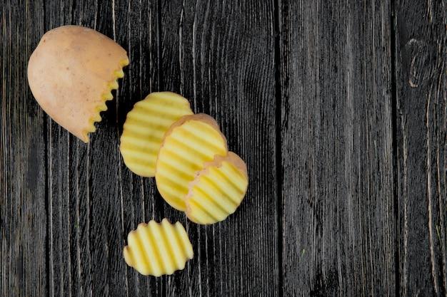 Vista cercana de rodajas de patata cortadas y en rodajas sobre fondo de madera con espacio de copia