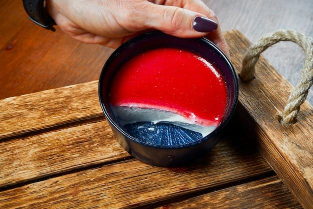 Vista cercana de la sabrosa panna cotta: un postre italiano de crema endulzada espesada con gelatina y moldeada con fresa en la mano del chef.