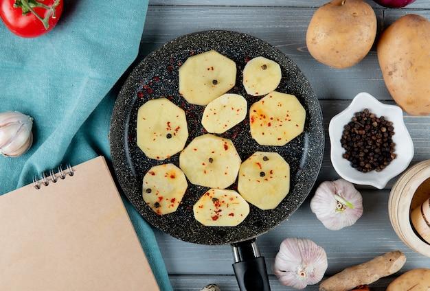 Vista cercana de la sartén llena de rodajas de patata con pimienta negra, ajo, jengibre sobre fondo de madera