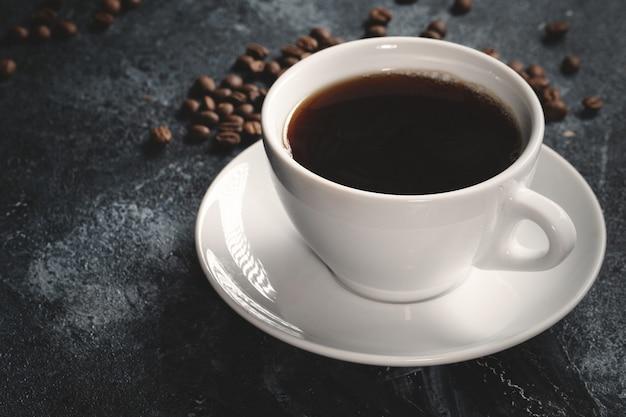 Vista cercana de semillas de café marrón con café en la oscuridad