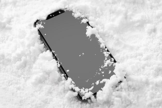 Vista cercana del smartphone en la nieve