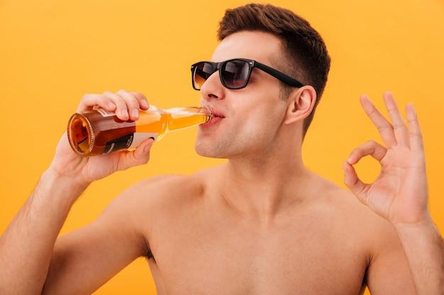 Vista cercana de sonriente hombre desnudo en gafas de sol bebiendo cerveza y mostrando bien firmar sobre amarillo