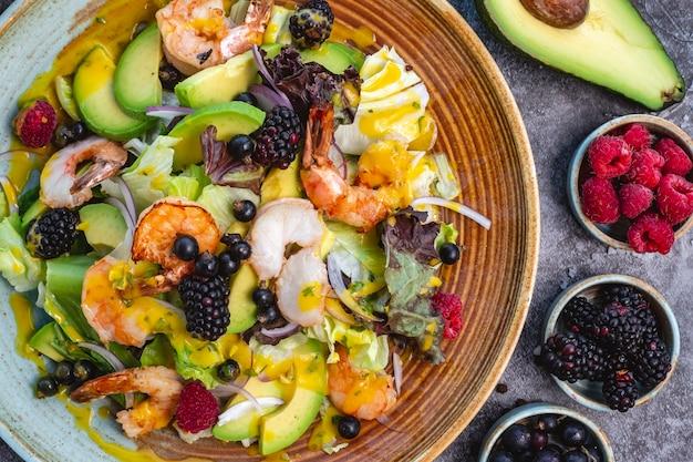 Vista cercana superior de ensalada de dieta saludable con camarones fritos, aguacate, lechuga, cebolla roja y bayas