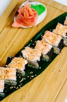 Vista cercana superior de rollos de sushi nori cubiertos con camarones servidos con jengibre
