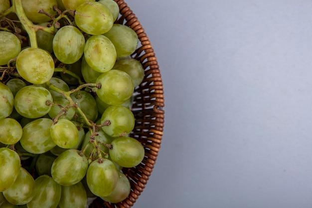 Vista cercana de uva blanca en canasta sobre fondo gris con espacio de copia
