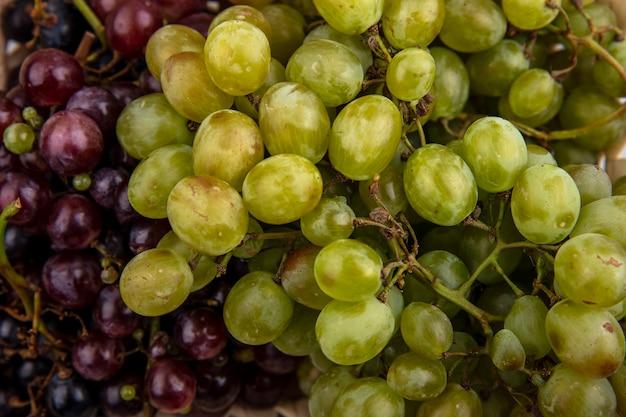 Vista cercana de uvas blancas y negras para usos de fondo