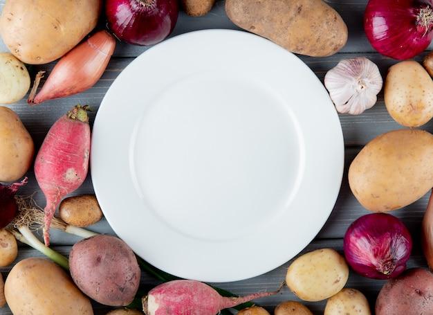 Vista cercana de verduras como rábano cebolla ajo patata con plato vacío en el centro
