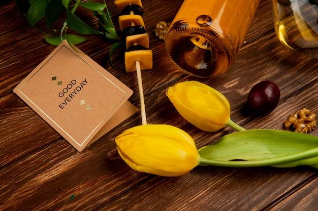 Vista cercana de vino blanco con queso cheddar y nuez uva buena tarjeta todos los días y flores en la mesa de madera