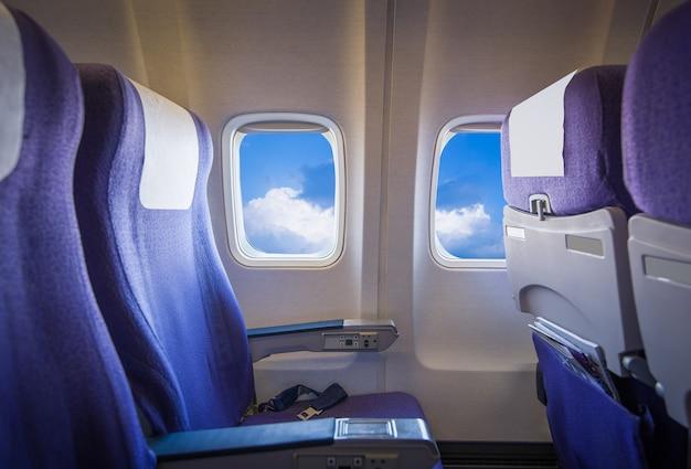 Vista del cielo y las nubes con luz solar desde la ventana del avión, asientos vacíos.