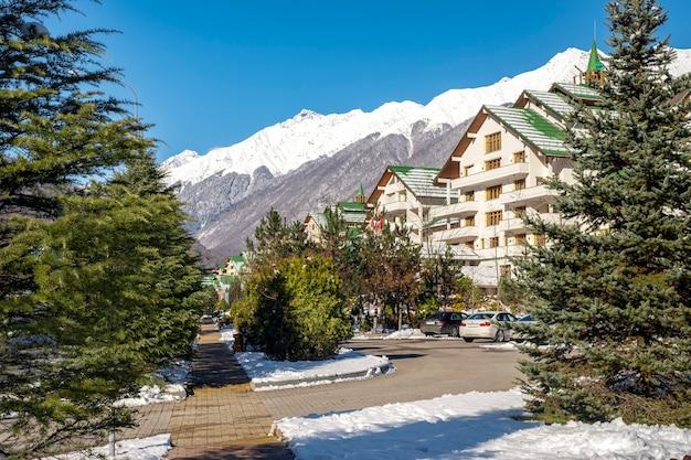 Vista clásica postal de casas de vacaciones en las montañas en un soleado día de invierno. kavkazsky región rusia,