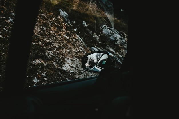 Vista de las colinas cubiertas de nieve y los árboles capturados desde la ventanilla de un automóvil y el espejo lateral