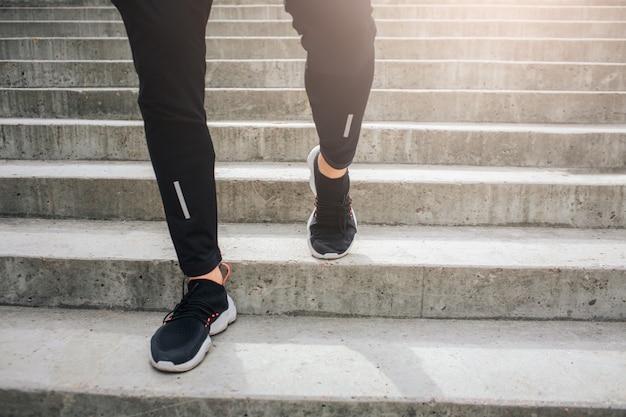 Vista cortada de las piernas del hombre. son fuertes y bien construidos. guy usa pantalones y zapatos deportivos. él hace bajar.