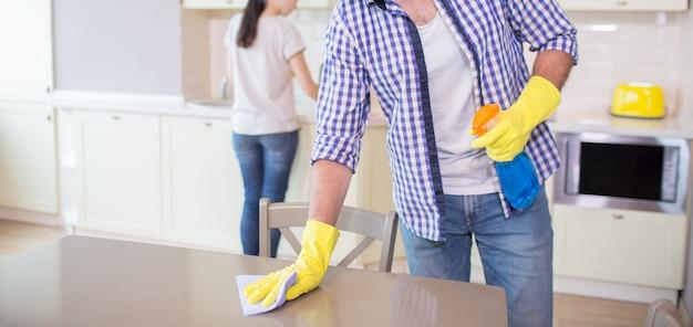 Vista de corte del hombre limpiando la superficie de la mesa de madera. lleva guantes amarillos. guy usa un trapo azul para limpiar. su esposa está haciendo lo mismo más adelante.