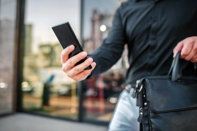 Vista de corte del hombre parado en el edificio exterior. él sostiene el teléfono y la bolsa.