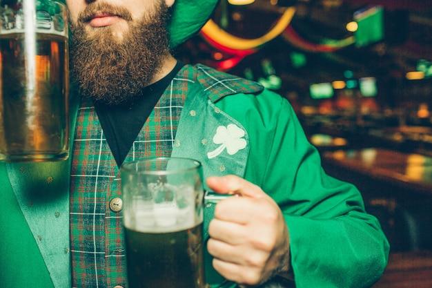 Vista de corte de hombre serio en pub. él sostiene dos jarras de cerveza. chico usa el traje de san patricio.