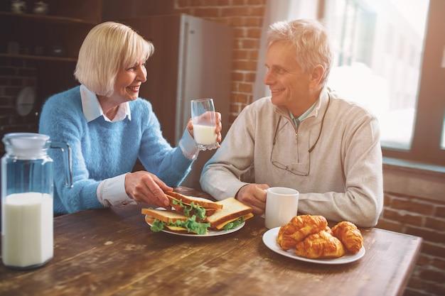 Vista de corte de personas mayores sentadas en la cocina y bebiendo leche