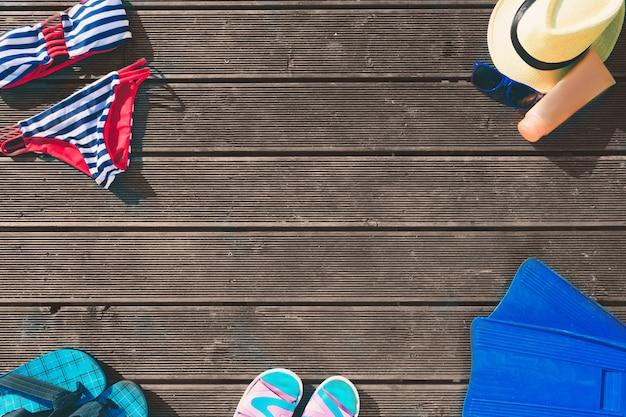 Vista de corte de ropa de verano. sombrero. traje de baño femenino. chancletas. aletas crema protectora contra el sol en botella de naranja. suelo de madera.