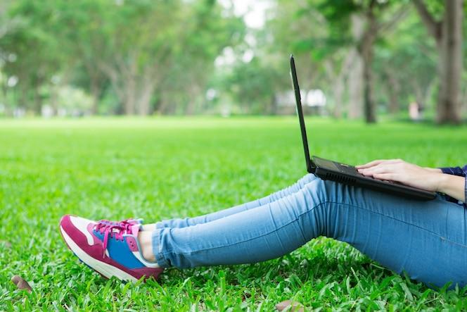 Vista cosechada de la muchacha que se sienta en hierba con la computadora portátil