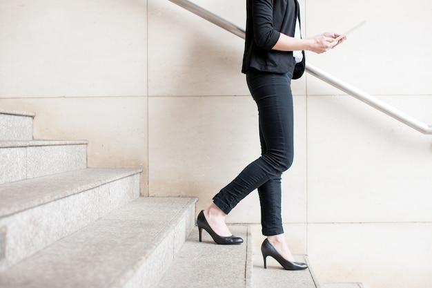 Vista cosechada de la señora del negocio que camina abajo de las escaleras