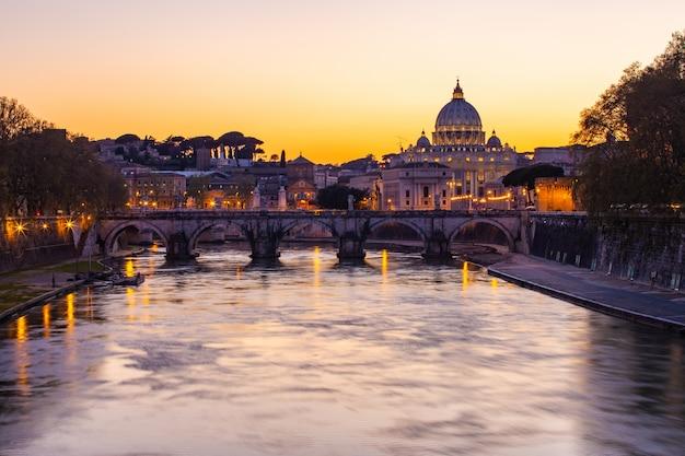 Vista crepuscular de la basílica de san pedro con el río tíber en roma, italia
