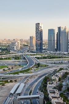 Vista de un cruce de carreteras con automóviles en movimiento en el fondo de una ciudad moderna