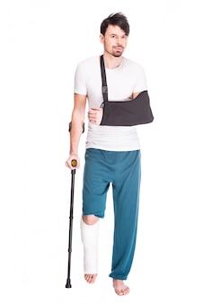 Vista de cuerpo entero de un hombre joven con una pierna rota.