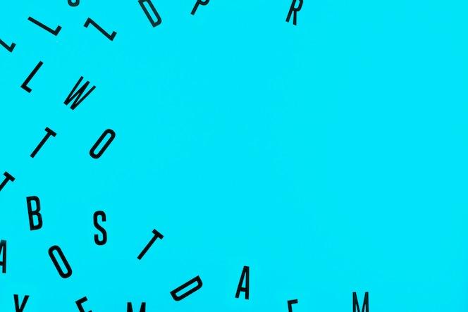Vista de ángulo alto de diferentes alfabetos negros sobre fondo azul