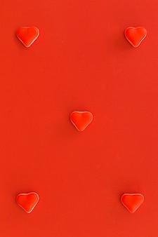 Vista de ángulo alto de dulces caramelos rojos sobre fondo rojo
