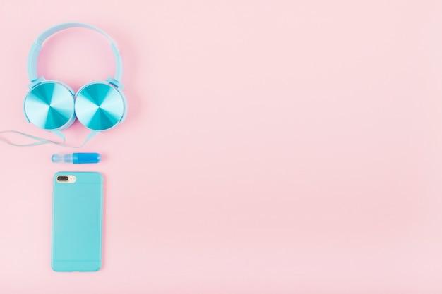 Vista de ángulo alto de teléfono inteligente y auriculares en fondo rosa