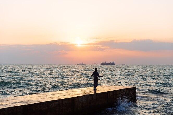 Vista de longitud completa del joven deportista saltando con cuerda de saltar, en el muelle, cerca del mar.
