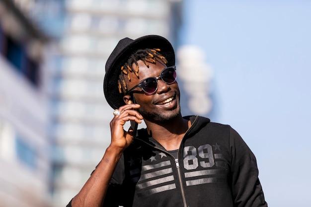 Vista delantera del hombre negro con las gafas de sol y el sombrero que se oponen a paisaje urbano en la calle mientras que usa un teléfono móvil en día soleado.