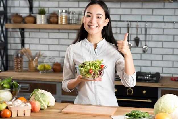 La vista delantera de la mujer joven feliz que sostiene el vidrio del cuenco con la ensalada que muestra el pulgar para arriba firma adentro la cocina