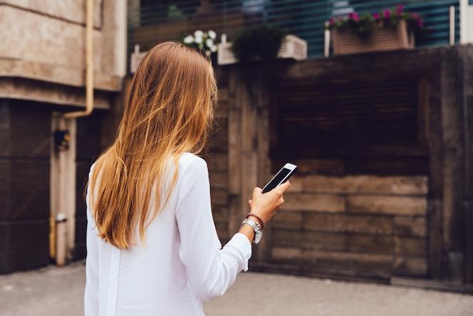 Vista desde la parte posterior de la mujer elegante con el pelo largo y rubio, usando un teléfono móvil