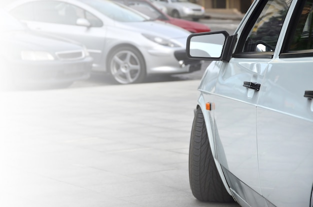 Vista diagonal de un automóvil brillante blanco que se encuentra en un cuadrado de azulejos grises
