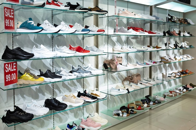 Vista diagonal de estantes de vidrio con zapatos de moda, zapatillas y zapatillas.