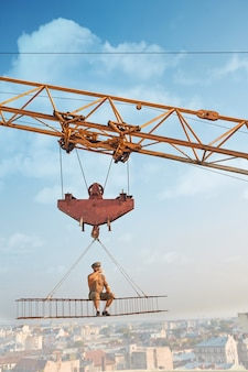 Vista desde la distancia de la grúa más grande que sostiene la construcción de hierro, donde el constructor sentado y comiendo. hombre descansando y mirando hacia abajo. paisaje urbano de fondo. edificio extremo en lo alto.