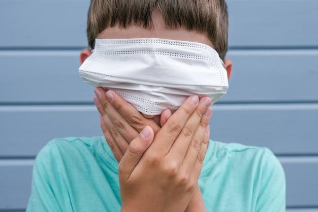 Una vista divertida de un niño con una máscara médica quirúrgica protectora blanca en los ojos en lugar de la boca y cubriéndose la boca con las manos, problemas de ocultación y hechos, mentiras sobre la epidemia y la pandemia.