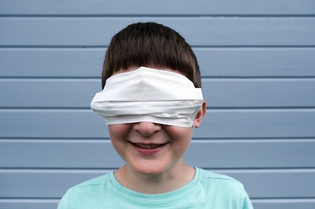 Una vista divertida de un niño sonriente vistiendo una máscara médica quirúrgica protectora blanca en sus ojos en lugar de una boca,