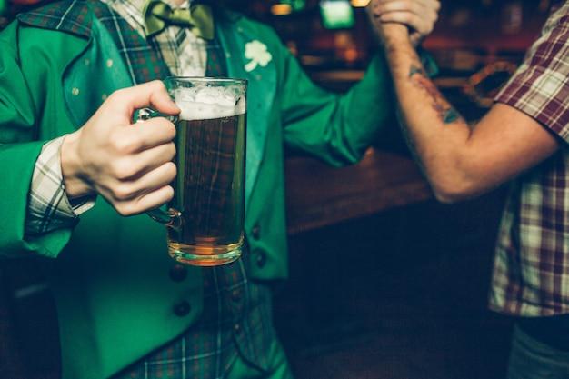 Vista de dos hombres tomados de la mano. chico de traje verde tiene jarra de cerveza. se paran adentro en el pub.