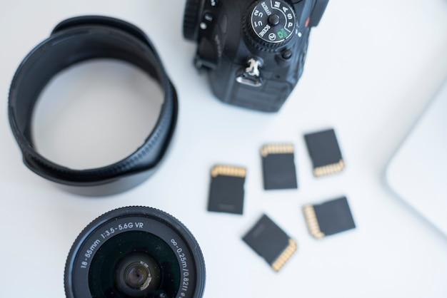 Vista elevada de los accesorios de la cámara con tarjetas de memoria en el escritorio.