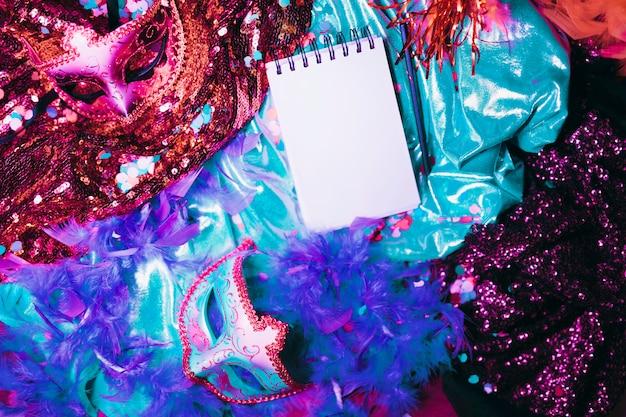 Vista elevada de accesorios de carnaval con bloc de notas espiral en blanco