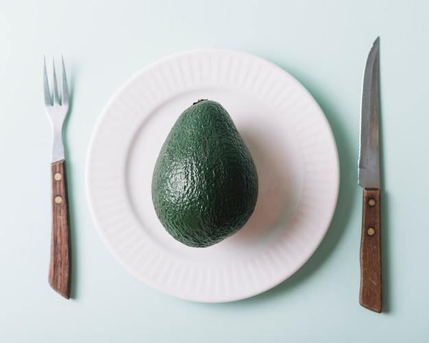 Vista elevada de aguacate en placa cerca de cuchillo y tenedor sobre fondo verde