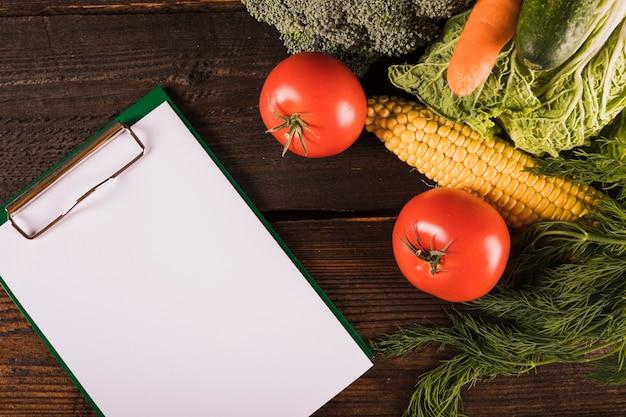 Vista elevada de alimentos frescos y saludables con portapapeles en blanco en el escritorio de madera