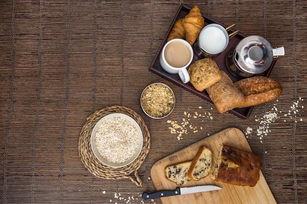 Vista elevada de alimentos horneados, té, leche y avena en mantel individuales