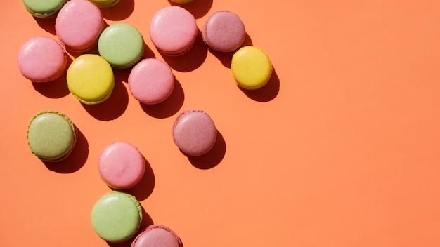 Una vista elevada de amarillo; macarrones rosados y verdes sobre fondo coloreado