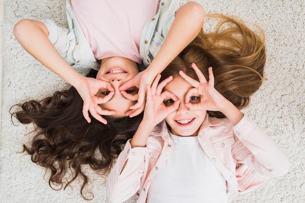 Una vista elevada de una amiga dos tendida en la alfombra haciendo un gesto aceptable como binocular mirando hacia arriba
