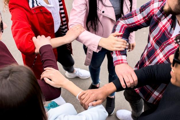 Vista elevada de amigos buzos tomándose las manos de los demás de pie en la calle