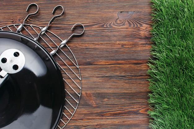 Vista elevada del aparato de barbacoa y pincho metálico sobre fondo de madera