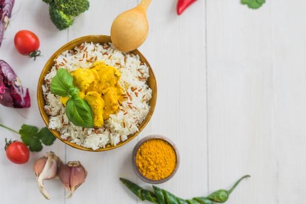 Vista elevada de arroz frito con pollo y hojas de albahaca con ingredientes sobre fondo blanco